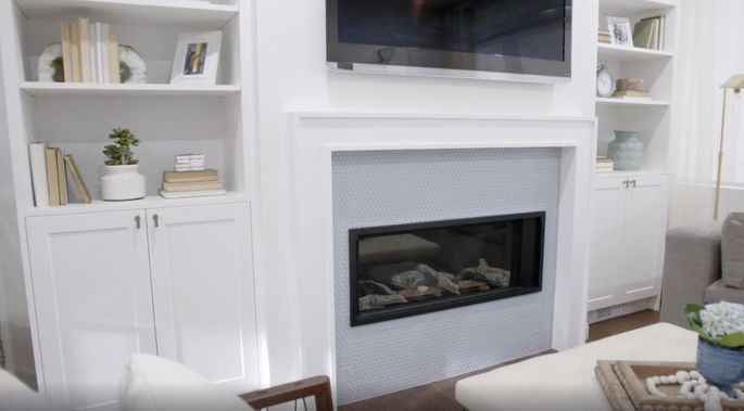 This fireplace adds a soft pop of color to the updated living room.