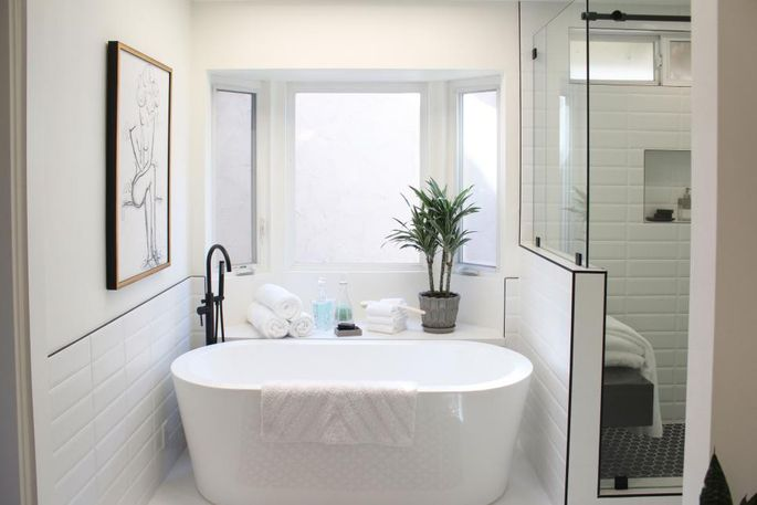 A free-standing tub with a new tile ledge alongside it