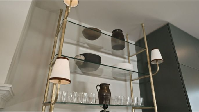 Berkus and Brent's unique shelf has light fixtures attached.
