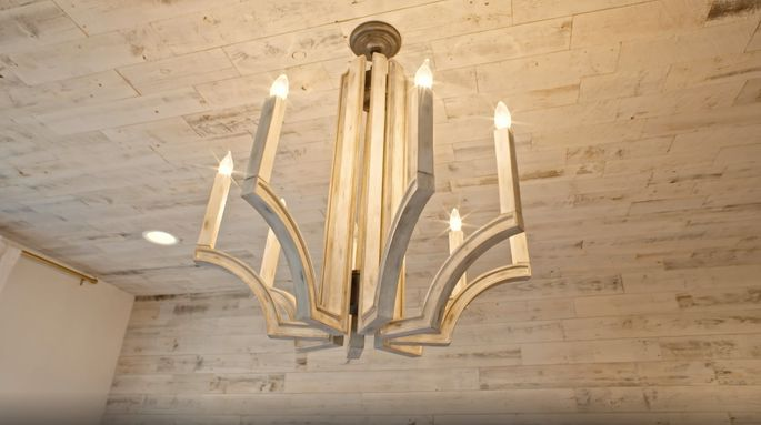 The lighting fixture echoes the reclaimed wood of the headboard wall.